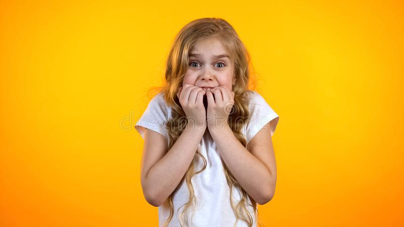 Extremely scared girl biting fingers and looking to camera, childish fears royalty free stock photography