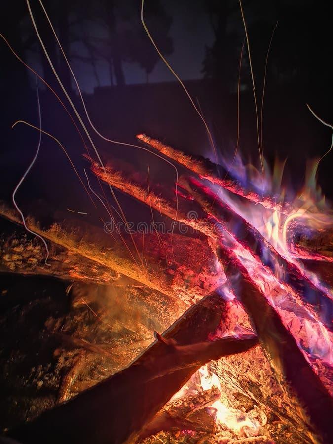 Extremer Abschluss oben von den Feuerfunken, die auf dunklem nächtlichem Himmel als schwarzer Hintergrund kommt von warmes Freien stockfotografie