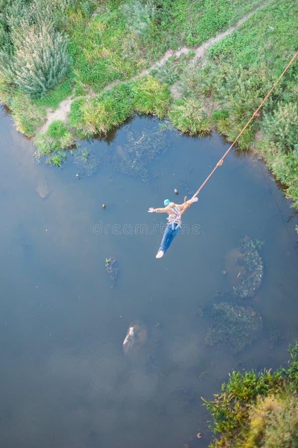 Extremer Sprung von der Br?cke Der Mann springt ?berraschend schnell in das Federelement, das am Himmel-Park springt, erforscht e stockfoto