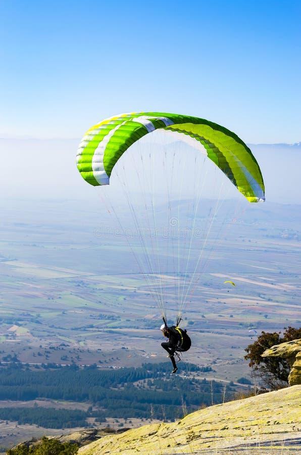 Extremes Gleitschirmfliegen, Mannbetrieb und Springen, um die Klippe zu entfernen lizenzfreie stockfotografie