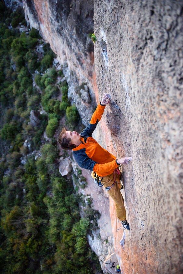 Extremes Sportklettern Im Freienlebensstil Felsenbergsteiger, der einer Klippe anhaftet stockfotos