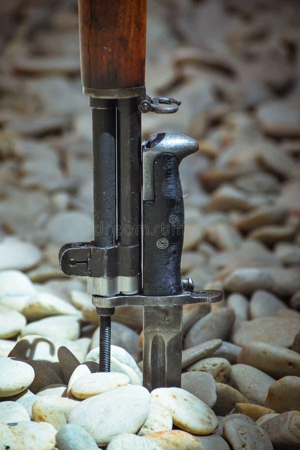 Extremidad de la bayoneta clavada en los rollos del río Concepto de la guerra/de la paz foto de archivo