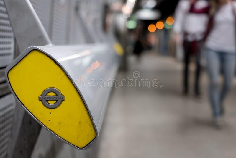 Extremidade do corrimão na estação subterrânea de Westminster, Londres que mostra o roundel de TFL No fundo assinantes borrados fotografia de stock royalty free