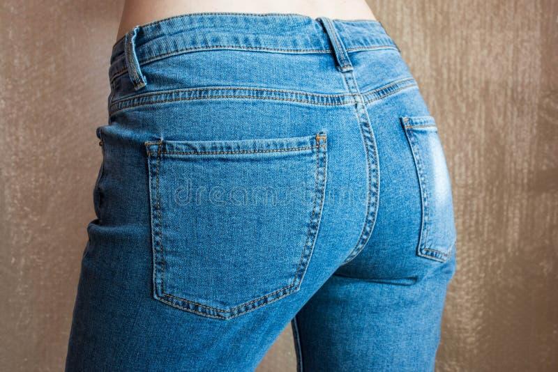 Extremidade fêmea magro apta na calças de ganga Nádegas da mulher na sarja de Nimes foto de stock royalty free