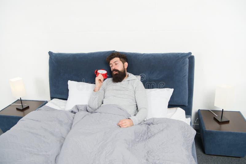 Extremidades para despertar temprano Cama soñolienta barbuda de la cara del hombre con el despertador en cama Qué ruido terrible  fotografía de archivo libre de regalías
