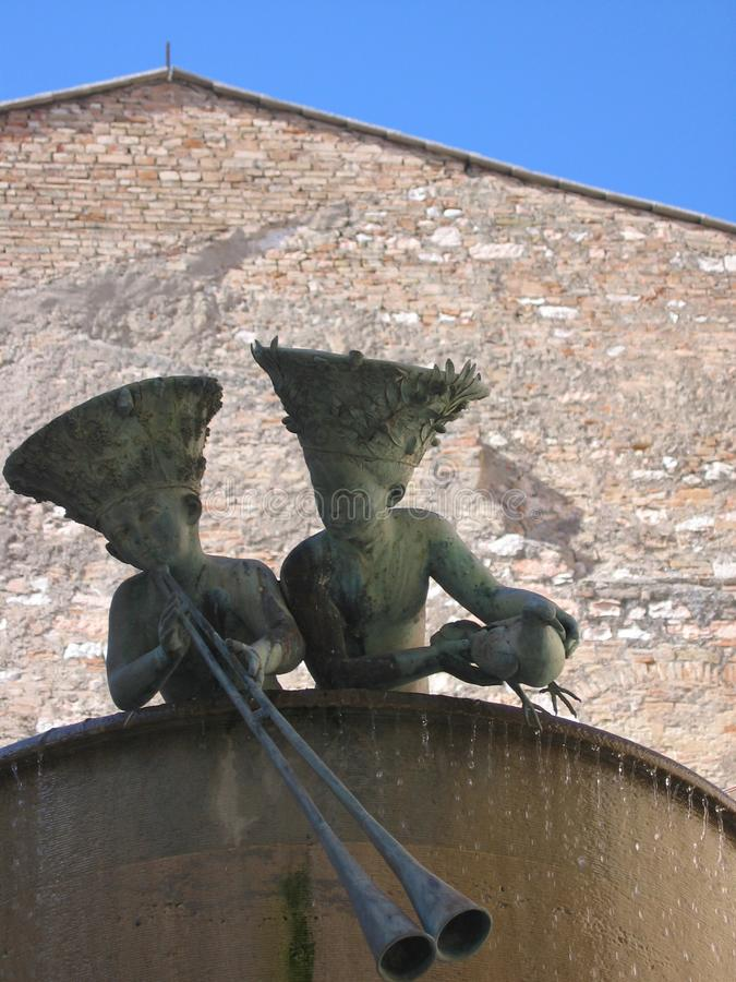 Free Extremity Of A Fountain With Statues Of Two Children With Big Hats That Lean Out With Behind An Ancient Church To Foligno, Italy. Stock Images - 110414654