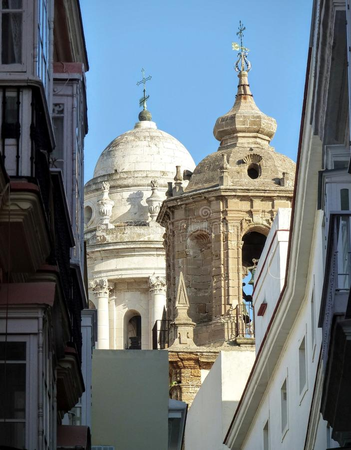 Extremity of two bell towers of different style in a narrow road of Cadiz in Andalusia in Spain. Blue clear sky. Sunny hot day. Travel destination. Summertime royalty free stock photography