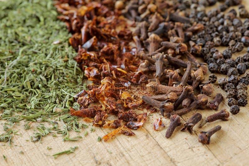 Extremo cercano para arriba de hierbas y de especias en una tabla de cortar de madera Tiro macro de sabroso, de la paprika, del c imagenes de archivo