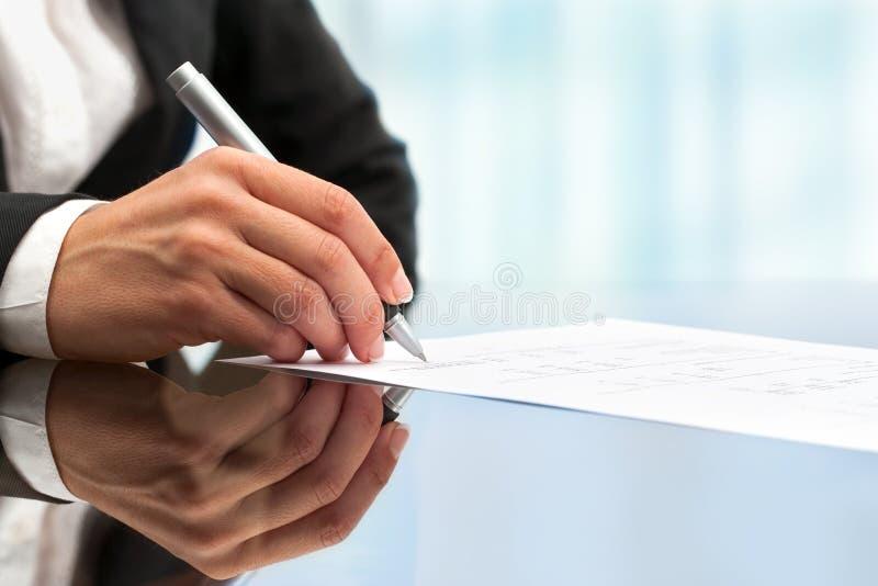 Extremo cercano para arriba del documento de firma de la mano femenina. foto de archivo