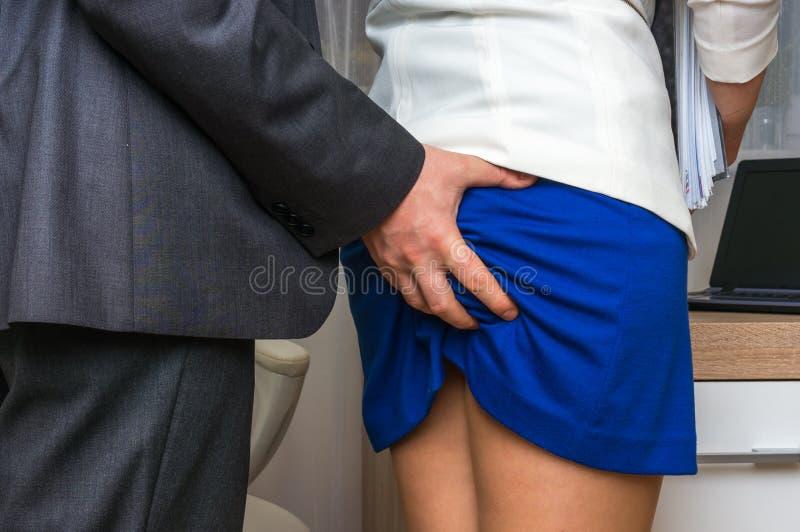 Extremo conmovedor del ` s de la mujer del hombre - acoso sexual en oficina foto de archivo libre de regalías