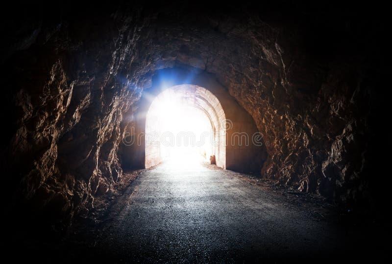 Extremo del túnel oscuro con la luz azul mágica imagen de archivo