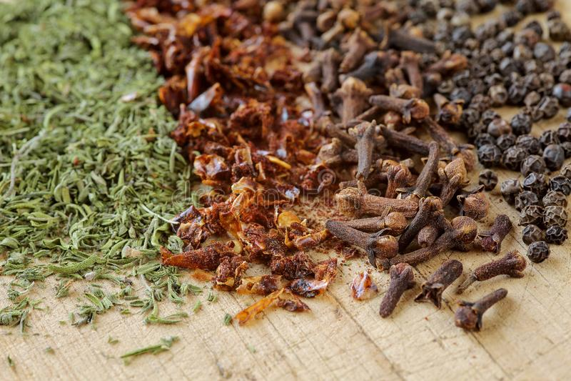 Extremo próximo acima das ervas e das especiarias em uma placa de corte de madeira Tiro macro da segurelha, da paprika, do cravo- imagens de stock