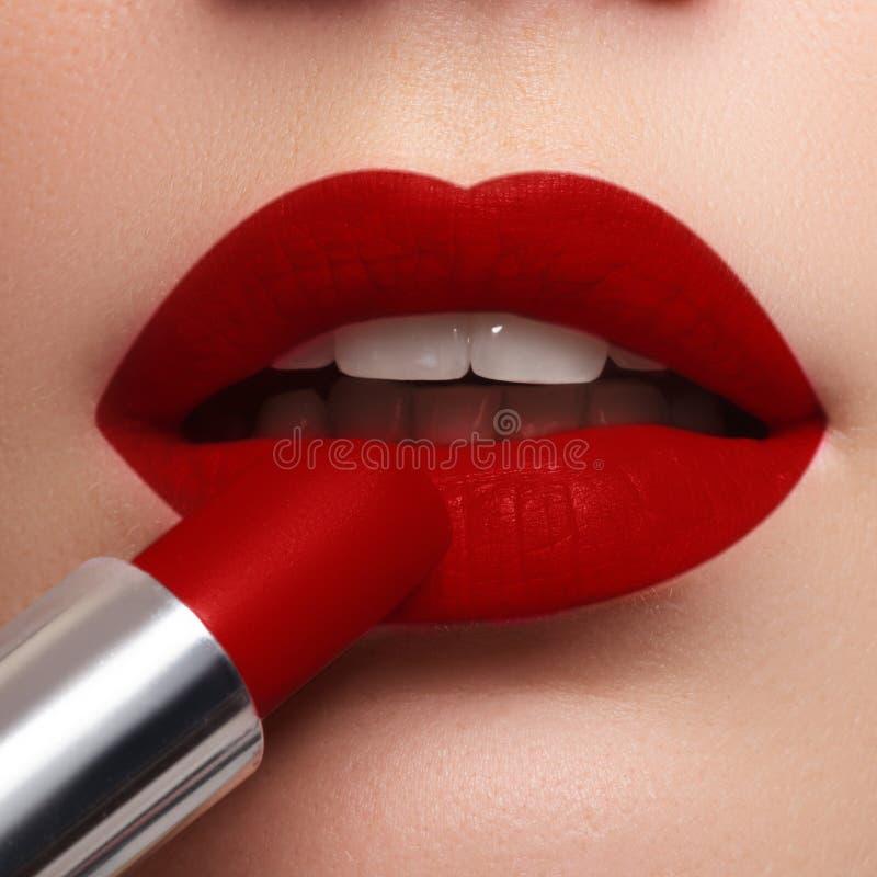 Extremo próximo acima no modelo que aplica a obscuridade - batom vermelho composição PR imagens de stock royalty free