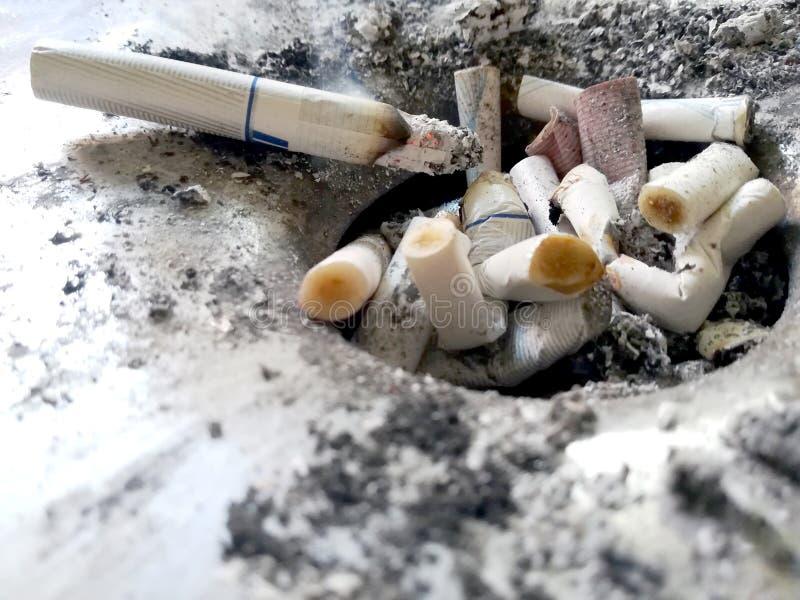 Extremos de cigarrillo en un cenicero del público del metal imágenes de archivo libres de regalías