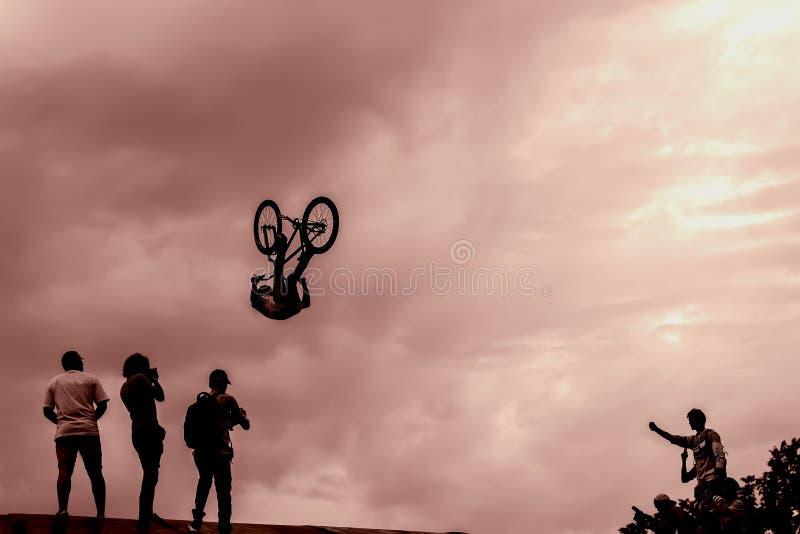 Extremsport en risico prestaties bij competities Het silhouet van de niet geïdentificeerde jonge mens voert stunts op uit stock foto