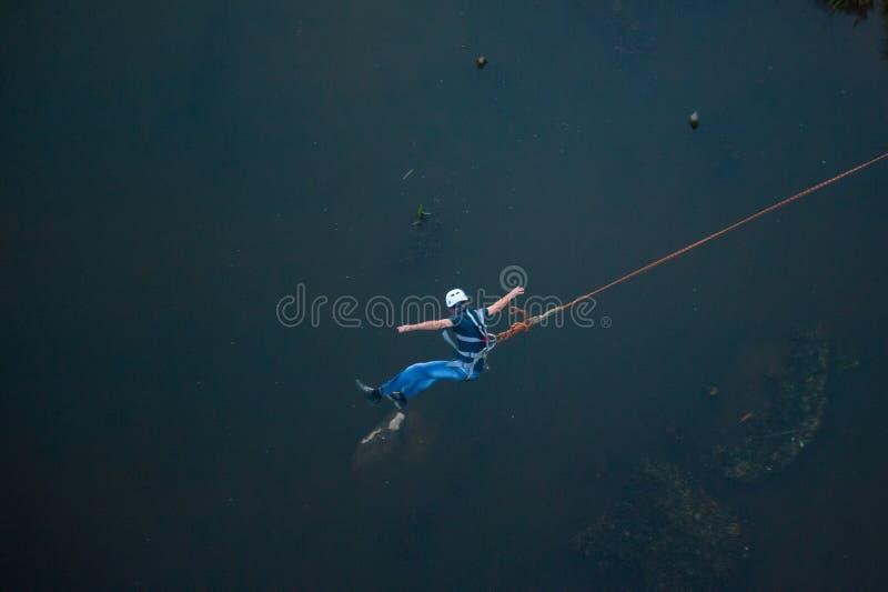 Extremt hopp fr?n bron Mannen hoppar i bungee som hoppar p? himmel, parkerar f?rv?nansv?rt snabbt unders?ker extrem gyckel Bungee royaltyfri fotografi