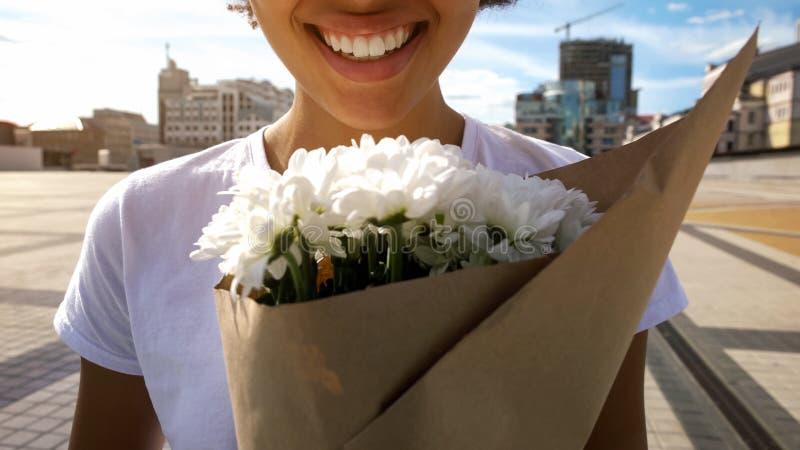 Extremt lycklig afro--amerikan flicka som rymmer den härliga buketten av blommor som ler royaltyfria foton