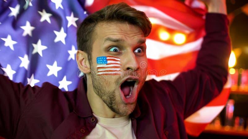 Extremt lycklig amerikansk nationsflagga för innehav för fotbollfan som firar mål, seger royaltyfri foto