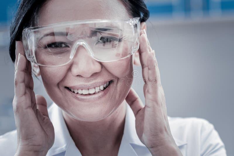 Extremt lycklig dam som justerar hennes säkerhetsexponeringsglas arkivbild