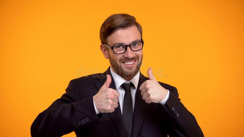 Extremt lycklig kontorsarbetare som visar upp tummar, lyckad investering, avtal royaltyfri foto