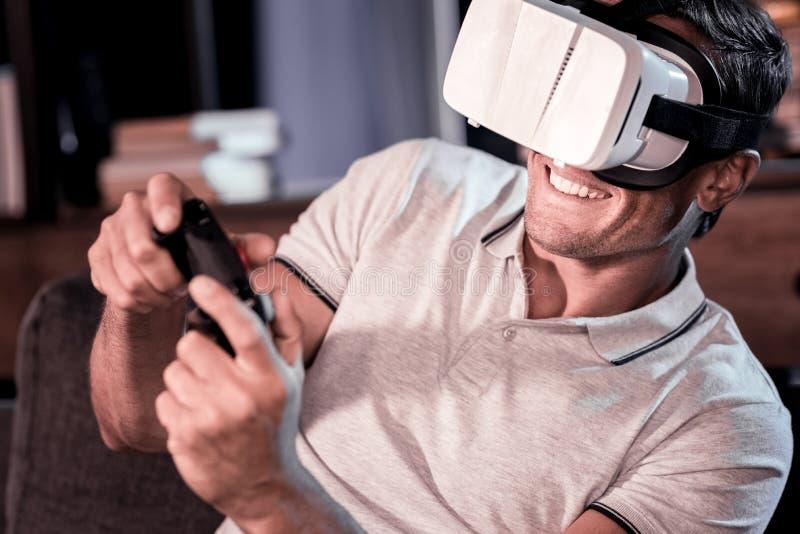 Extremt lycklig man som hemma spelar videospel arkivfoto