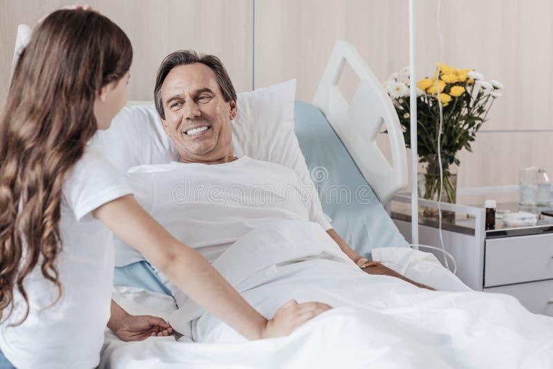 Extremt lycklig man som ler, medan se dottern i sjukhus royaltyfri bild