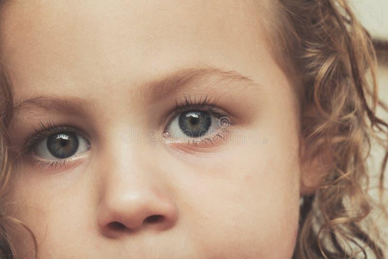 Extremt slut upp den härliga för litet barnflicka för blåa ögon ståenden - det extrema slutet för barnframsida upp med kopierings royaltyfri foto