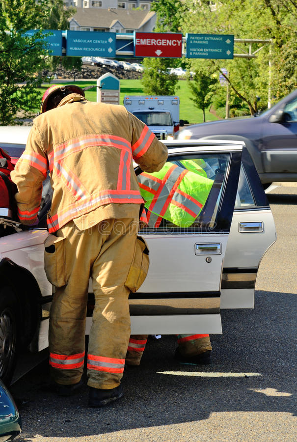 Extrication. Fire fighters and paramedic emt personnel extricate the victim of a two vehicle head on accident at an intersection in Roseburg, OR on August 27 royalty free stock image