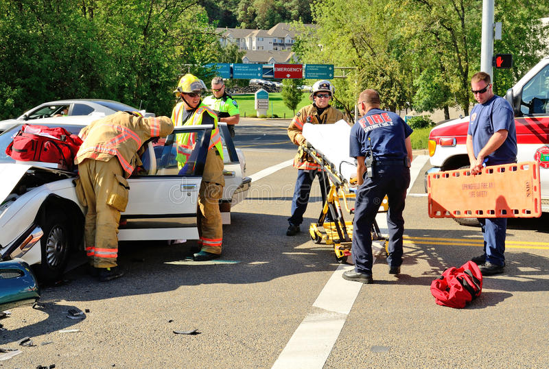 Extrication. Fire fighters and paramedic emt personnel extricate the victim of a two vehicle head on accident at an intersection in Roseburg, OR on August 27 stock photo