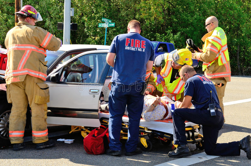 Extrication. Fire fighters and paramedic emt personnel extricate the victim of a two vehicle head on accident at an intersection in Roseburg, OR on August 27 royalty free stock photography