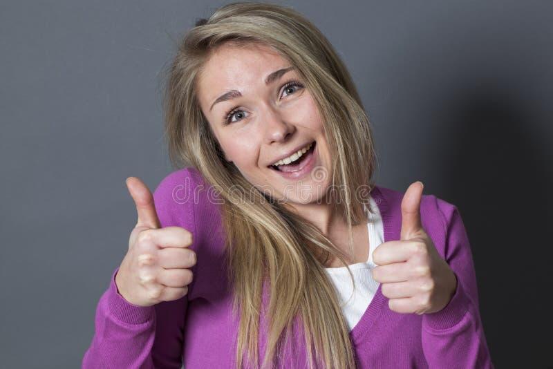 Extrovertierte Frau 20s mit den doppelten Daumen oben stockbilder