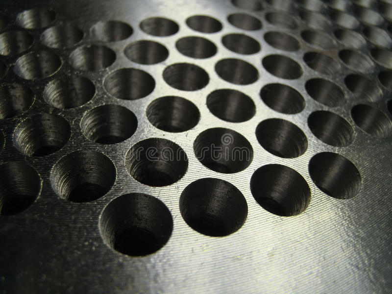 Extruder detail with numerous holes. Many holes drilled in a shiny metal plate for matrix extruder detail stock photo