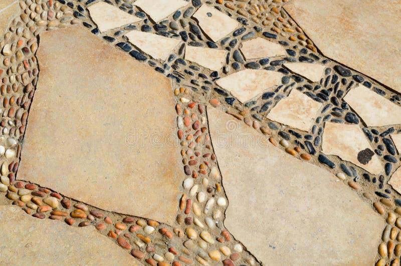Exture av vägen läggas ut ur liten rund vitbrunt, och svartstenar och granit fragmenterar från kullersten med modeller arkivbilder