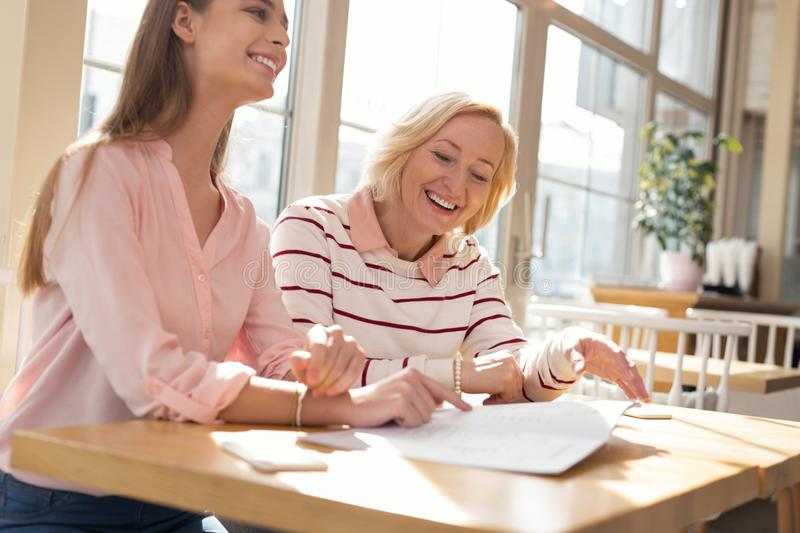 Exuberant granny discussing family business with her granddaughter. In high spirits. Content loving granny discussing family business with her granddaughter royalty free stock image