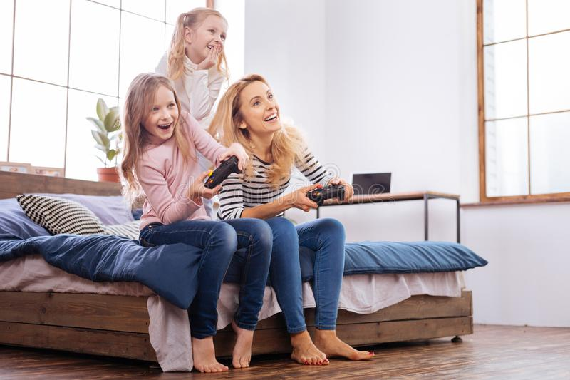 Exuberant kleine zusters die met hun moeder spelen stock foto