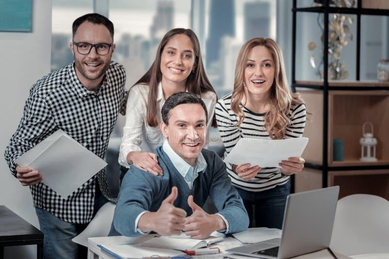 Exuberant teamleden die zich bij hun collega bevinden royalty-vrije stock foto