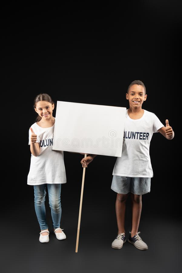 Exuberant volunteers holding a white table royalty free stock image
