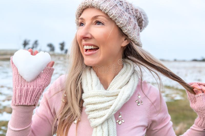 Exuberant woman holding a heart of snow. Exuberant happy woman holding a heart of snow in her hand royalty free stock image