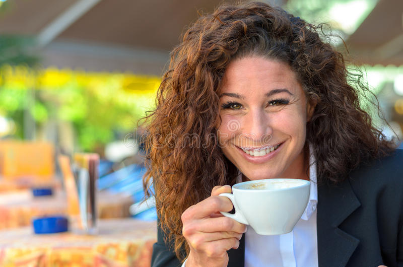 Exultant jonge vrouw die van een kop van koffie genieten stock foto's