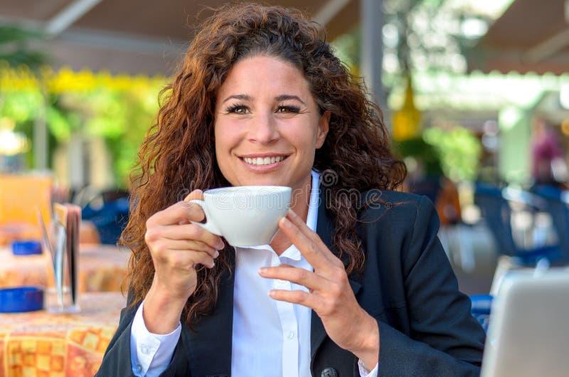 Exultant jonge vrouw die van een kop van koffie genieten royalty-vrije stock afbeeldingen