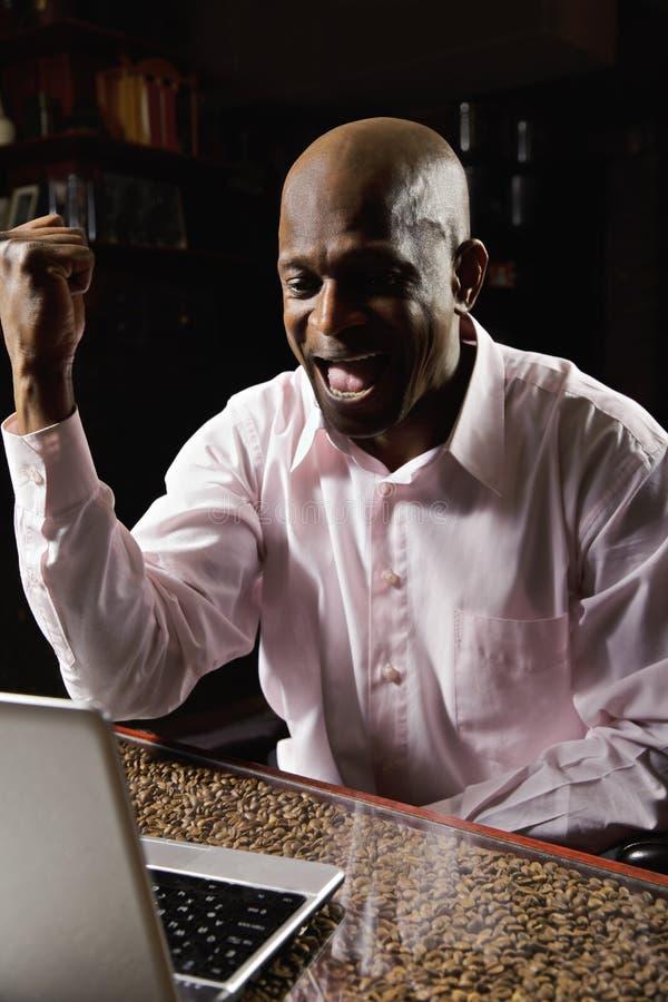 Exultant kerel met laptop royalty-vrije stock afbeelding