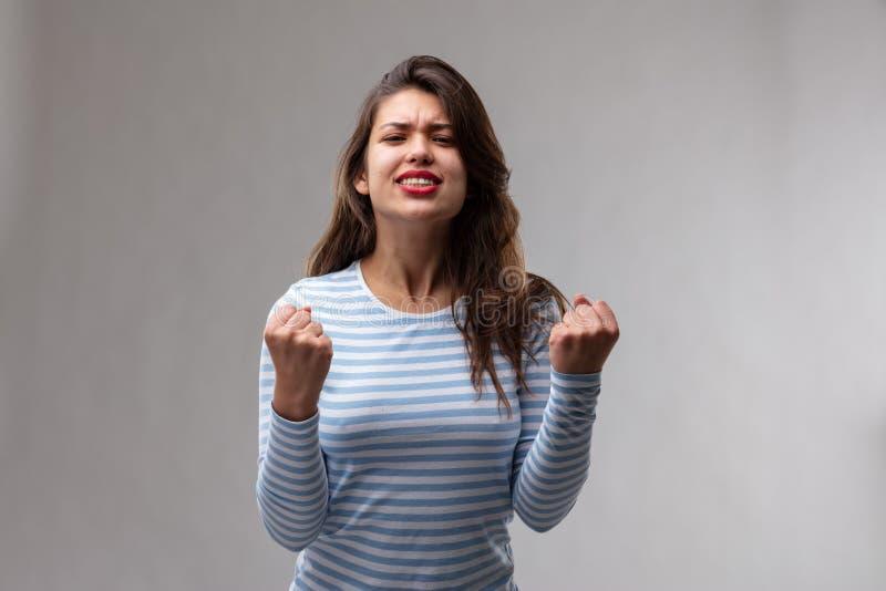 Exultant opgewekte jonge vrouw die haar vuisten dichtklemmen stock fotografie