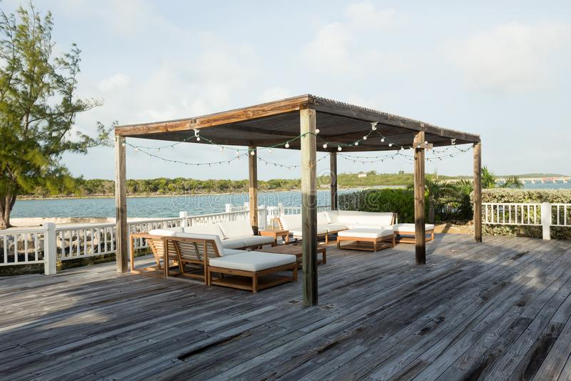 Exuma outdoor patio. Luxury outdoor patio deck with furniture, canopy, and view of the water, located in Exuma, Bahamas stock photos