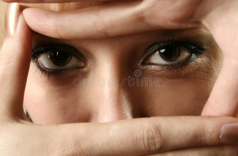 Eye. The female person covered with hands stock image
