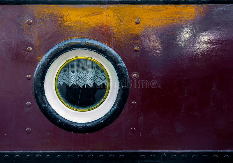 The eye of the barge. Porthole and small lace on a dock, textures and metallic colors royalty free stock photography