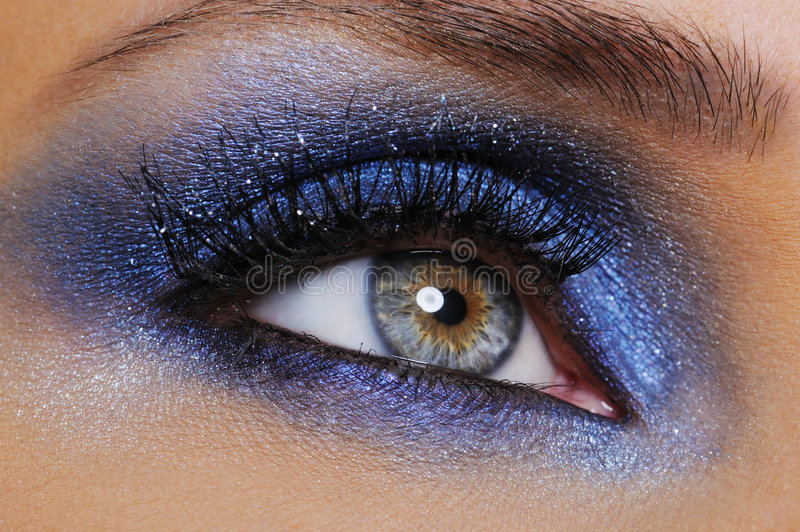 Eye with bright blue eyeshadow stock photography