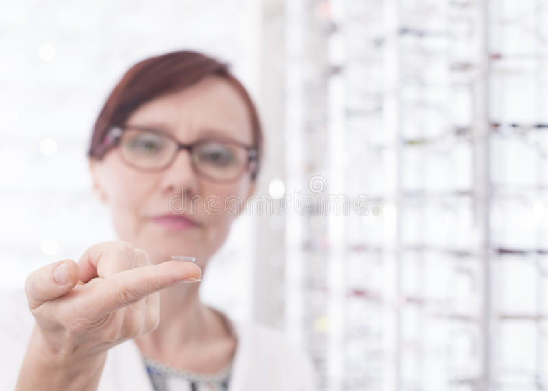 Eye Care. Hands of a woman holding a contact lens stock photography