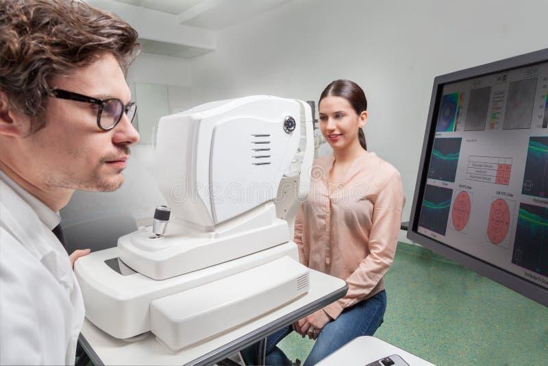 Eye care professional doing an OCT SLO retinal analysis. L`oftalmologo nella clinica oculistica esamina la funzione visiva retinica con una macchina OCT SLO royalty free stock photography