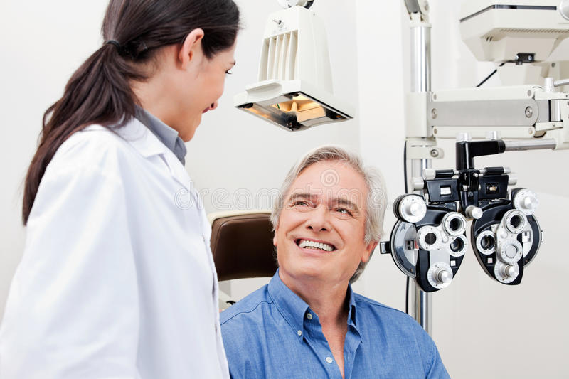 Eye Checkup. Smiling mature patient consulting with optometrist for an eye checkup stock image