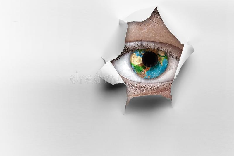 Eye in a hole of torn paper stock images